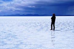 Salar de Uyuni Bolivia salt desert - lonely man standing. Salar de Uyuni Bolivia - panorama of the perfect white flat salt desert with blue cloudy sky. Lonely stock images