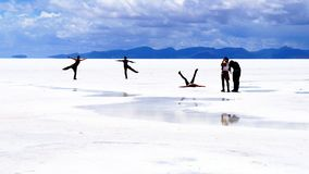 Salar de Uyuni Bolivia salt desert - people posing. Salar de Uyuni Bolivia - panorama of the perfect white flat salt desert with blue cloudy sky Stock Photography