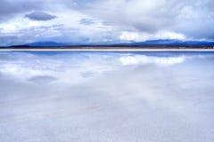 Salar de Uyuni reflection of blue sky on salt desert. Salar de Uyuni - panorama of the flat salt desert with blue cloudy sky mirrored in the wet surface and Royalty Free Stock Photos