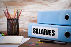 Salaries, Office Binder on Wooden Desk. On the table colored pen Royalty Free Stock Photo