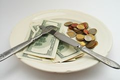 Salary for food. Banknotes and coins on a plate as a meal Stock Photo