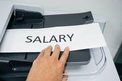 Salary on the printer. Hold a paper of salary on the printer for copy Royalty Free Stock Photography