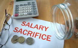 Salary sacrifice. With coins on paper and in pot and calculator behind Stock Photo