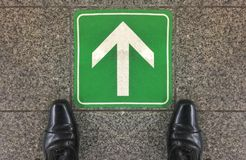 A salaryman shoes standing on the floor which has go forward direction sign. Stock Image