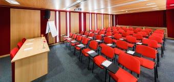 Salas de conferencias interiores rojas con el flipchart y un proyector Imagen de archivo