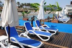 Salas de estar do Chaise do sol em uma praia Foto de Stock Royalty Free