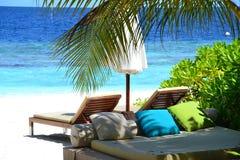 Salas de estar de Sun em uma praia fotografia de stock