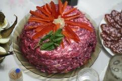 Salat 'Hering unter einem Pelzmantel ', verziert mit Scheiben des Gemüsepaprikas lizenzfreies stockbild