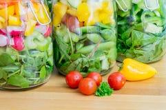 Salat in den Glasspeichergläsern Abschluss oben Stockfoto