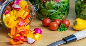 Salat in den Glasspeichergläsern Gemüse, das aus einem heraus gießt Stockbilder