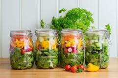 Salat in den Glasspeichergläsern Vier in einer ordentlichen Reihe Stockfotografie