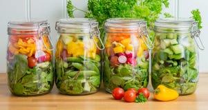 Salat in den Glasspeichergläsern Vier in einer Zeile Stockbild