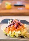Salat des geräucherten Lachses mit undeutlichem hölzernem Hintergrund des hackenden Brettes Stockfoto