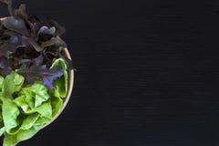 (2) Salat des Tones zwei in der hölzernen Schüssel auf dunkler hölzerner Tabelle Lizenzfreie Stockfotos