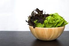 (2) Salat des Tones zwei in der hölzernen Schüssel auf dunkler hölzerner Tabelle Stockfotografie