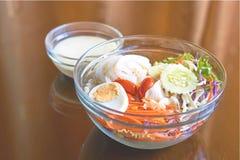 Salat in einer transparenten Glasschüssel mit Reflexion; orange Vorhanghintergrund Stockfoto