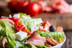 Salat Frischer Sommerkopfsalatsalat Gesunder Mittelmeersalatoliventomaten-Parmesankäseparmesankäse und Prosciutto Stockbilder
