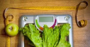 Salat, grüner Apfel, gelbes messendes Band und Gewichtsskala Lizenzfreie Stockfotos