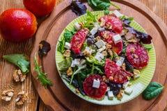 Salat: Mischung des grünen Salats, des Fetas, der roten Orangen und der Walnüsse stockfotografie