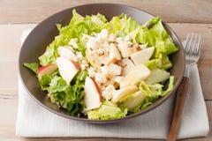 Salat mit Äpfeln und Walnüssen auf rustikalem hölzernem Hintergrund Stockfotos