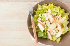 Salat mit Äpfeln und Walnüssen auf rustikalem hölzernem Hintergrund Stockfoto
