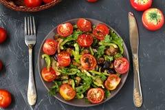 Salat mit Auberginen und Kirschtomaten auf einer dunklen Platte auf einem dunklen Hintergrund, Draufsicht stockfoto