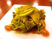 Salat mit Avocado- und Kirschtomaten mit japanischer Salatsoße auf weißem Teller - Nahaufnahme Stockfoto