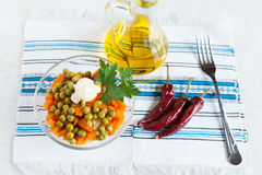 Salat mit in Büchsen konservierten Erbsen und Karotten. Schmieröl und Peperoni Lizenzfreies Stockfoto