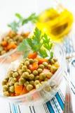 Salat mit in Büchsen konservierten grünen Erbsen und gekochtem Gemüse Stockbilder