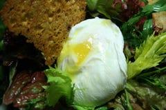 Salat mit Chips des poschierten Eies und des Brotes Stockfoto