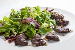 Salat mit der hühnerleber und den Kiefernnüssen auf einer weißen Platte lizenzfreie stockfotos