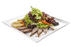 Salat mit Entenbrust auf einer weißen Platte lizenzfreie stockfotos