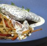 Salat mit Fischen in der Sahnesauce auf einer blauen Platte stockfotos