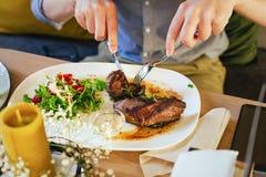Salat mit Fleisch auf einer Platte, auf einem Holztisch Männliche Hände mit einer Gabel und einem Messer, Schnittfleisch stockfotos
