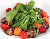 Salat mit gebackenen Kürbis und der hühnerleber. Stockfoto