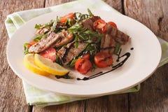 Salat mit gegrilltem Rindfleisch, Arugula, Tomaten und Balsamico-Essig Lizenzfreies Stockfoto