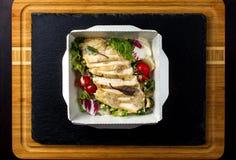 Salat mit Huhn auf einem Papierkasten Stockfotos