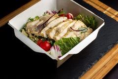 Salat mit Huhn auf einem Papierkasten Stockbild