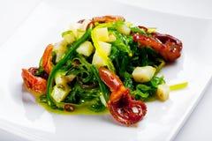 Salat mit Krake, Kamm-Muschel und Hiyashi Wakame Stockfotos