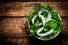 Salat mit messendem Band der Eignung über hölzernem Hintergrund würfel Stockfotos