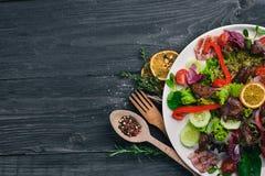 Salat mit Speck und der hühnerleber Auf einer hölzernen Oberfläche stockfotografie