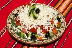 Salat mit Tomaten, Gurke, Paprika, schwarzen Oliven, Käse und Schinken Stockfotos