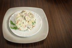 Salat Olivier in einer weißen Platte auf einem braunen hölzernen Hintergrund Stockfotos