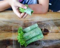 Salat rollt im klaren Plastikkasten Stockbilder