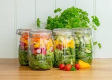 Salat in vier Glasspeichergläsern Stockfoto