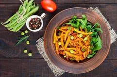 Salat von den grünen Bohnen, gedämpft mit Zwiebeln in der Tomatensauce und in den grünen Blättern von Arugula Lizenzfreies Stockfoto