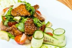 Salat von frischen Gurken und von Tomaten briet Fleisch auf einem Holztisch stockbild