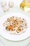 Salat von frischen Pilzen mit rotem Pfeffer, Olivenöl und Kräutern Stockbild