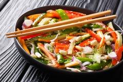 Salat von Gurken, von Pfeffern, von Karotten, von Erbsenhülsen mit indischem Sesam und von Erdnussnahaufnahme auf einer Platte ho lizenzfreie stockbilder