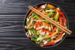 Salat von Gurken, von Pfeffern, von Karotten, von Erbsenhülsen mit indischem Sesam und von Erdnussnahaufnahme auf einer Platte ho lizenzfreie stockfotos